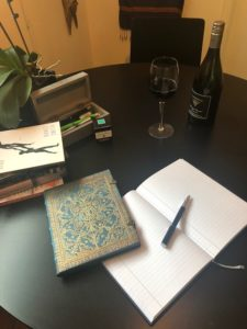 essentials for writing retreats notebook with glass of wine