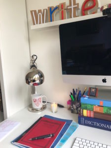 photo of writing desk with sign and mug that say Write
