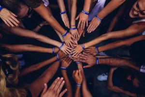 group of hands reaching to the center
