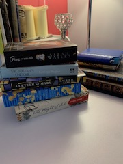 writer's reading list as a stack of novels on a writing desk