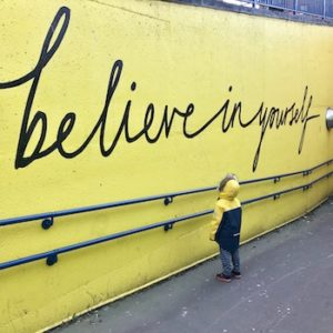 Why publish: believe in yourself [toddler looking at yellow graffiti on wall]