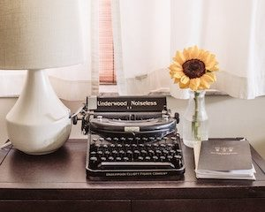 typewriter with sunflower in clear vase writing inspiration