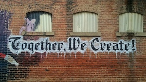Writing in Community: graffiti on brick wall says Together We Create