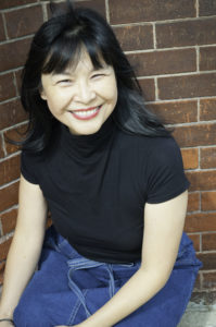 Canadian author Carrianne Leung seated, smiling in black t-shirt and jean skirt