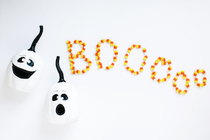 two plastic ghosts and candy corn spelling out boo afraid to write