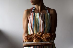 black woman wearing striped apron holding fancy loaf of bread recipe for consistent writing