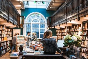 photo of bookstore with wooden shelves and blue wall should you write for the market