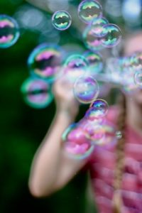 young woman in pink blowing bubbles writing as play metaphor