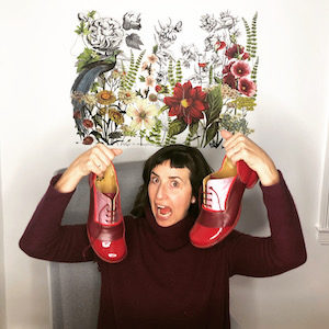 Christy Ann Conlin author photo for The Speed of Mercy Christy has dark hair and holds a pair of red Fluevogs