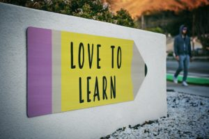 yellow sign in shape of a pencil says love to learn used to headline 7 online writing workshops